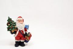 Święty Mikołaj przewożenia Bożenarodzeniowi prezenty na białym tle Obrazy Royalty Free