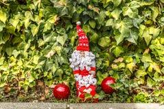 Święty Mikołaj siedzi w ogródzie z dwa Bożenarodzeniowymi piłkami Fotografia Royalty Free
