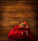 Święty Mikołaj torba, Bożenarodzeniowy Czerwony Sackful, Brown Drewniany tło zdjęcia stock
