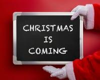 Święty Mikołaj trzyma czarną kredową deskę pisze z bożymi narodzeniami PRZYCHODZI na czerwieni obraz royalty free