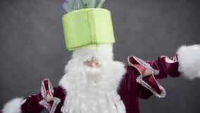 Święty Mikołaj trzyma prezent na jego głowie zdjęcie wideo