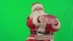 Święty Mikołaj trzyma prezent w jego ręce na zieleni zbiory wideo