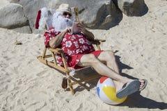 Święty Mikołaj używa pastylkę lub czytelnika na plaży Obrazy Royalty Free