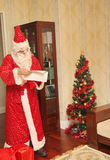 Święty Mikołaj w długim jaskrawym kostiumu i rękawiczkach dostaje prezenty od dużej czerwonej torby - Rosja, Moskwa, 07 Grudzień, Zdjęcie Stock