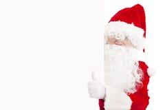 Święty Mikołaj wskazuje przy pustym sztandarem z kciukiem up Obraz Stock