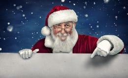 Święty Mikołaj wskazuje w białym puste miejsce znaku z uśmiechem Zdjęcia Royalty Free