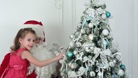 Święty Mikołaj z ładną małą dziewczynką dekoruje choinki zdjęcie wideo