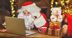 Święty Mikołaj z komputerem przed bożymi narodzeniami obraz royalty free