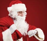 Święty Mikołaj z torbą teraźniejszość i patrzeć jego zegarek. Boże Narodzenia. obraz royalty free