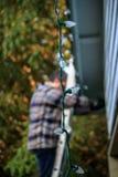 Światła wieszają puszek gdy mężczyzna próby dekorować do domu Zdjęcie Stock