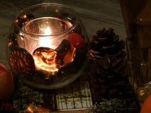 Światło świeczki, sosna konusuje i rezerwuje zdjęcie stock