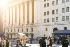 Światło słoneczne błyszczy na tłumach ludzie i historyczni budynki wzdłuż Wall Street w pieniężnym okręgu niski Manhattan, Nowym obraz stock