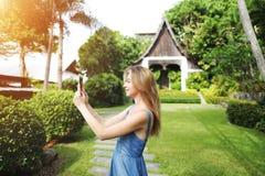 Światło słoneczne portret bierze, ono uśmiecha się na zielonych palmach młoda kobieta fotografię z pastylką i domowego tło w Tajl zdjęcie royalty free