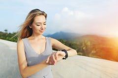 Światło słoneczne portret młoda blondynki dziewczyna używa smartwatch, góry w tle, Tajlandia obraz royalty free