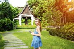 Światło słoneczne portret młodej kobiety mienia telefon, uśmiechnięty i patrzeć kamerę na, palmach i domowym tle zdjęcia stock