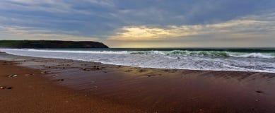 Światło słoneczne przez mgławej chmury nad piekła usta plażą Obraz Royalty Free
