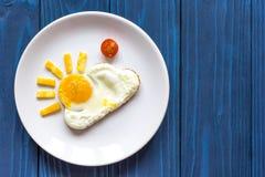 Światło słoneczne smażył jajka śniadaniowych dla dzieciaka na błękitnym tle obrazy royalty free