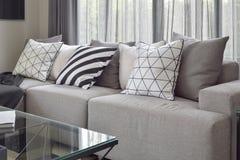 Światło - szara kanapa z zmienia deseniowe poduszki w livling kącie Zdjęcia Royalty Free
