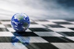 Świat na chessboard na niebieskiego nieba tle fotografia stock