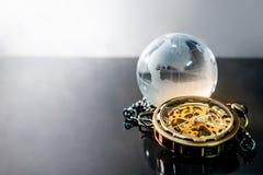 Światowej kuli ziemskiej krystaliczny szkło i kieszeniowy zegarek fotografia royalty free