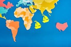 Światowej mapy cięcie z barwionego papieru i dwa cięcia z koloru żółtego papieru statków opierających się na błękicie Obrazy Royalty Free