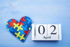 Światowy autyzm świadomości dzień, umysłowy opieki zdrowotnej pojęcie z łamigłówką lub wyrzynarka wzór na sercu z kalendarzem, obrazy royalty free