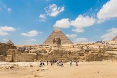 Światu Giza sławni ostrosłupy i Wielki sfinks z turystą fotografia royalty free