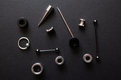 Świderkowaci akcesoria na czarnego tła metalu nierdzewnej biżuterii dla dziurawienie kochanków obraz royalty free