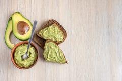 Świeża avocado śmietanka w drewnianym pucharze z chlebów plasterkami na lekkim tle Odgórny widok Z kopii przestrzenią obrazy royalty free