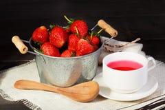 Świeża czerwona truskawka w wiadrze na czarnym drewnianym stole Zdjęcia Royalty Free