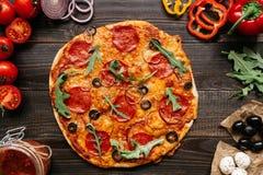 Świeża delisious pizza z pizza składnikami na drewnianym stole, odgórny widok obraz royalty free