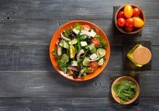 Świeża grecka sałatka w talerzu i składnikach Obrazy Stock