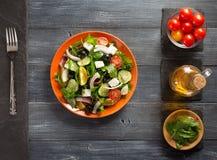 Świeża grecka sałatka w talerzu i składnikach Obrazy Royalty Free