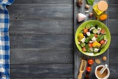 Świeża grecka sałatka w talerzu i składnikach Zdjęcie Royalty Free