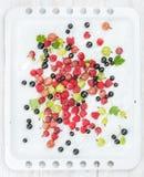 Świeża lato ogródu jagod rozmaitość na białej wypiekowej tacy nad lekkim drewnianym tłem Zdjęcia Royalty Free