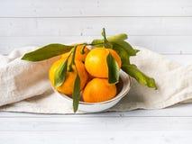 Świeża mandarynka lub tangerines z trzonami i liśćmi na talerzu na białej drewnianej tło kopii przestrzeni fotografia royalty free