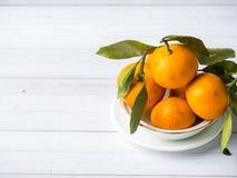 Świeża mandarynka lub tangerines z trzonami i liśćmi na talerzu na białej drewnianej tło kopii przestrzeni obraz stock