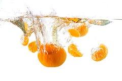 Świeża mandarynka spada w wodnym pluśnięciu, odosobnionym na bielu zdjęcie royalty free