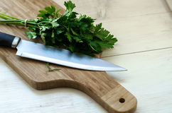 Świeża organicznie pietruszka z nożem na drewnianej tnącej desce Obraz Royalty Free