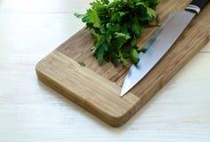 Świeża organicznie pietruszka z nożem na drewnianej tnącej desce Fotografia Royalty Free