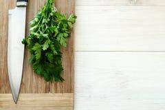 Świeża organicznie pietruszka z nożem na drewnianej tnącej desce Obrazy Royalty Free