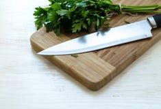 Świeża organicznie pietruszka z nożem na drewnianej tnącej desce Obraz Stock