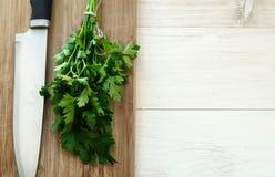 Świeża organicznie pietruszka z nożem na drewnianej tnącej desce Fotografia Stock