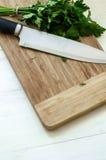Świeża organicznie pietruszka z nożem na drewnianej tnącej desce Zdjęcia Royalty Free