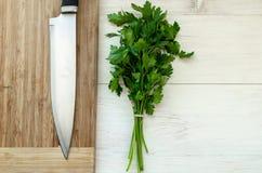 Świeża organicznie pietruszka z nożem na drewnianej tnącej desce Zdjęcia Stock