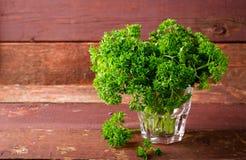 Świeża organicznie zielona kędzierzawa pietruszka w szkle Zdjęcia Stock