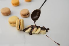 Świeża owoc banan z czekoladowym kumberlandem nalewał dalej z łyżką i macaroon ciastkami Zdjęcia Stock