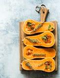 Świeża pomarańczowa muszkatołowa bania, cięcie w połówce, przygotowywającej dla piec z pikantność i ziele na drewno desce na popi fotografia stock