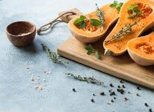 Świeża pomarańczowa muszkatołowa bania, cięcie w połówce, przygotowywającej dla piec z pikantność i ziele na drewno desce na popi zdjęcie stock