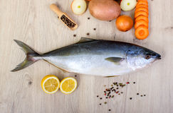 Świeża ryba z cytryną, pietruszką i pikantnością na drewnianej tnącej desce odizolowywającej, zdjęcie royalty free